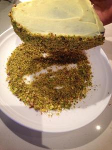 Placing pistachios on sides of cake