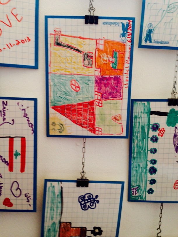 Children's art work hangs on the wall of the workshop room, at MACAM.