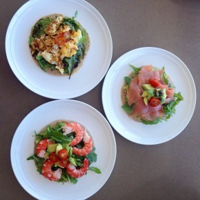 A trio of Salmon, prawns and scrambled eggs with avocado and baby rocket on a gluten, dairy and yeast free pancake.