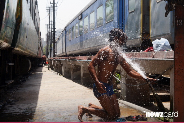 An Indian man washes himself at a water pipe to cool down at a railway station in New Delhi on May 22, 2013. Heatwave conditions continued in the Indian capital, with temperatures registering a record high for the month of May at 45.6 degrees celsius. AFP PHOTO/RAVEENDRAN (Photo credit should read RAVEENDRAN/AFP/Getty Images)